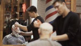 理发师在理发店喷洒parfume一个成熟客户 股票录像