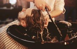 理发师在理发店洗他的有香波的头发 r 图库摄影