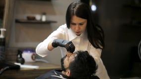 理发师女孩做有普通刀片的理发胡子客户 影视素材