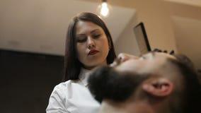 理发师女孩做有普通刀片的理发胡子客户 股票视频