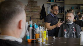 理发师对他的客户的饰物胡子 葡萄酒沙龙,主要服务人 灰发的人,和年龄的 股票录像