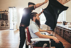理发师投入板料盖他的从被剪的头发的客户 免版税图库摄影