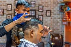 理发师理发理发店的一名顾客 免版税库存图片