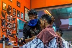 理发师理发理发店的一名顾客 免版税图库摄影