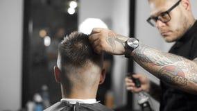 理发师由浪花弄湿头发并且梳他们, tattoed理发师做顾客的理发在理发店,人` s理发 影视素材