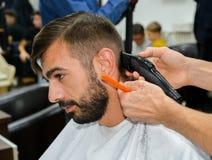 理发师男性理发在我们的天 免版税库存照片