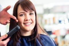 理发师礼服有平的铁的妇女头发在商店 免版税库存图片
