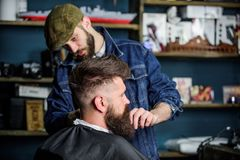 理发师繁忙与行家客户,在背景的秀丽供应修饰胡子  有用海角盖的胡子的行家 免版税库存照片