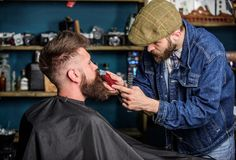 理发师繁忙与行家客户,在背景的秀丽供应的修饰髭 有胡子和髭的行家 免版税库存照片