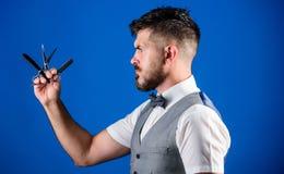 理发师胡子修饰技巧 人背心有蝶形领结举行普通刀片蓝色背景 理发师葡萄酒艺术概念 库存图片