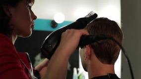 理发师`的s一个人 烘干人` s头的女性美发师使用由hairdryer 股票录像