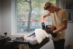 理发椅的一个英俊的人得到由有一把剃刀的一位理发师刮了在被弄脏的轻的背景 图库摄影