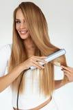 理发 有美丽的长的头发的妇女使用直挺器 库存图片