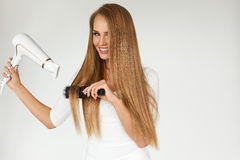理发 烘干美丽的健康长的直发的妇女 免版税库存图片