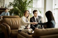 经理和客户的握手在合同讨论以后在现代办公室的大厅 免版税库存照片