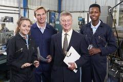 经理和职员画象在工程学工厂 免版税库存照片