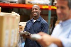 经理在有工作者扫描箱子的仓库里在前景 免版税库存图片