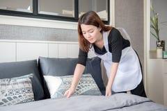 整理床的年轻佣人在旅馆客房,清洗的服务概念 免版税库存图片