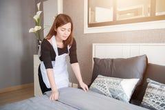 整理床的年轻佣人在旅馆客房,清洗的服务概念 免版税库存照片