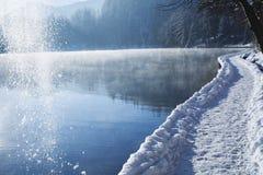 理想的节假日 在湖旁边的冬天道路 雪是下跌的f 免版税库存照片