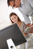 经理谈话与有片剂的妇女在手上 免版税库存照片
