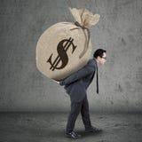 年轻经理运载的金钱袋子 免版税库存照片