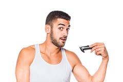 整理他的胡子的年轻英俊的人 免版税库存照片
