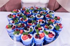 琐事 很多琐事或蛋糕在一块蓝色玻璃装饰用莓果 在玻璃的欢乐层状点心 免版税库存图片