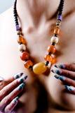 琥珀色的项链和艺术性的修指甲 免版税图库摄影