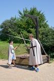 琥珀,俄罗斯- 2016年7月26日:有男孩的人奖牌雨衣的在剑作战 中世纪战斗的模仿 免版税库存图片