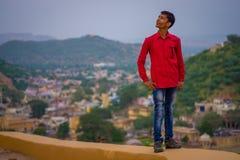 琥珀,印度- 2017年9月19日:关闭穿一件红色T恤杉的一个未认出的印地安人有城市的斜纹布裤子 免版税库存照片