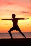 瑜伽人训练和思考在战士姿势 免版税库存图片