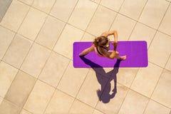 瑜伽位置的少妇在晴天,室外,从ab的看法 图库摄影