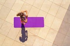 瑜伽位置的少妇在晴天,室外,从ab的看法 免版税图库摄影