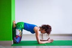 瑜伽位置的少妇对墙壁 免版税库存图片