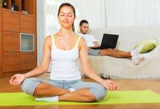 瑜伽位置的轻松的女孩和懒惰人 库存照片