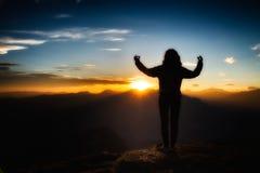 瑜伽凝思的女孩在日落的一座山顶部 免版税库存图片