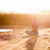 瑜伽凝思,日落的妇女 免版税图库摄影