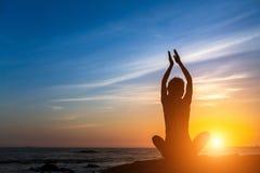 瑜伽剪影在海洋的妇女凝思在日落期间 库存图片