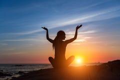 瑜伽剪影 海洋的凝思妇女在美好的日落期间 库存照片