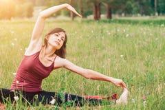 瑜伽和凝思本质上在一个晴天 伯根地上面的美丽的妇女在领域背景  免版税库存图片