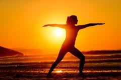 瑜伽和在海滩放松在日落 免版税库存图片