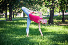 瑜伽在公园,户外,妇女` s健康,瑜伽妇女 健康生活方式和休闲的概念 灵活的年轻人 免版税图库摄影
