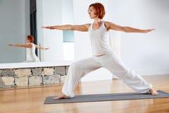 瑜伽在木地板的战士两II姿势 库存图片