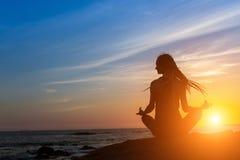 瑜伽在海洋的妇女剪影在日落期间 免版税图库摄影