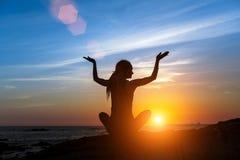 瑜伽在海洋海滩的妇女剪影在惊人的日落期间 凝思 库存图片