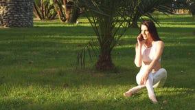 瑜伽女孩坐草,谈话在智能手机在公园 股票视频