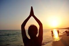 瑜伽妇女凝思在日出海边 免版税库存照片