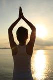 瑜伽妇女凝思在日出海边 免版税库存图片