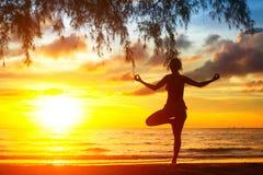 瑜伽妇女剪影,在海滩的锻炼在美好的日落期间 免版税图库摄影